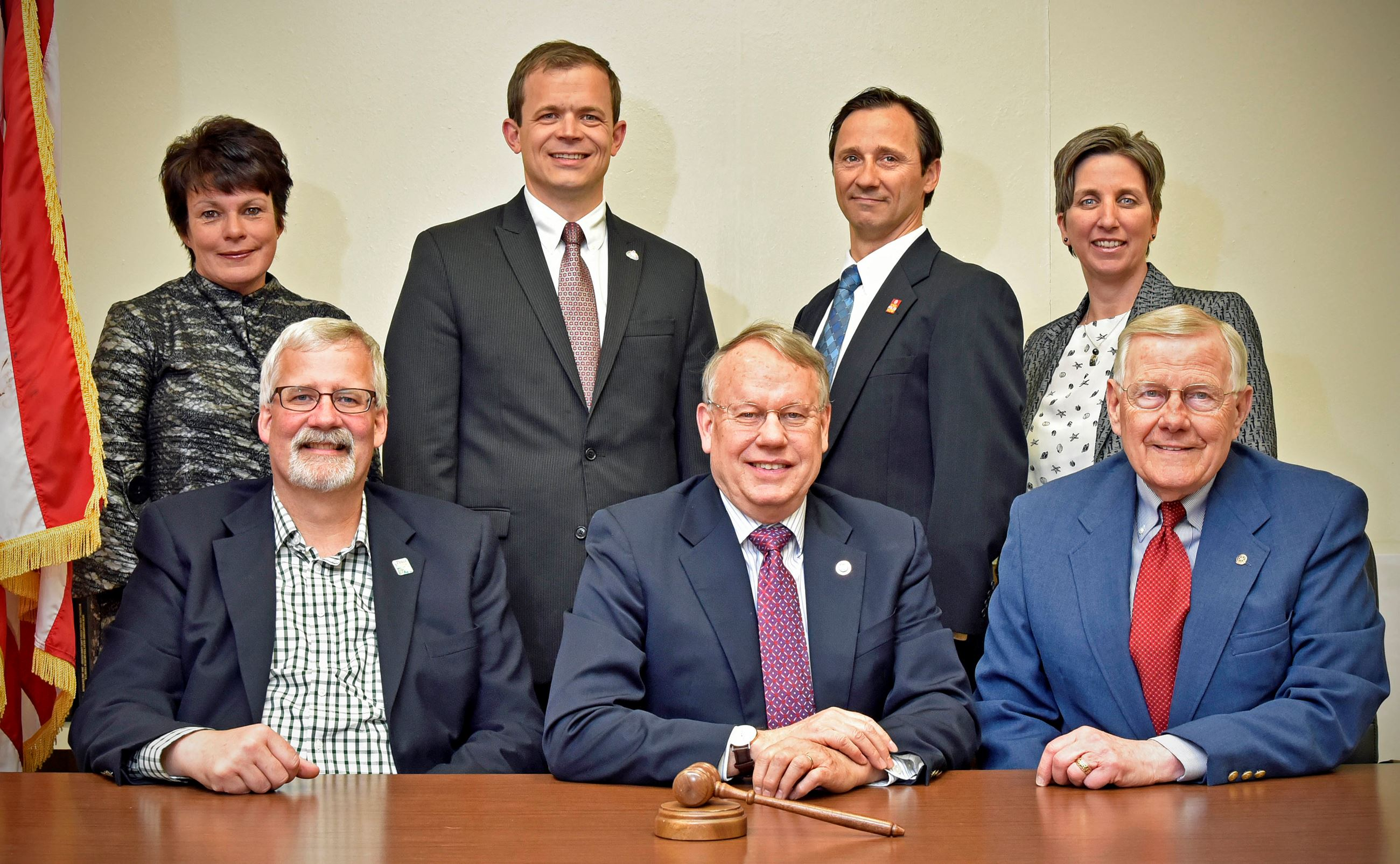 Five men and two women in business attire, with American flag behind them