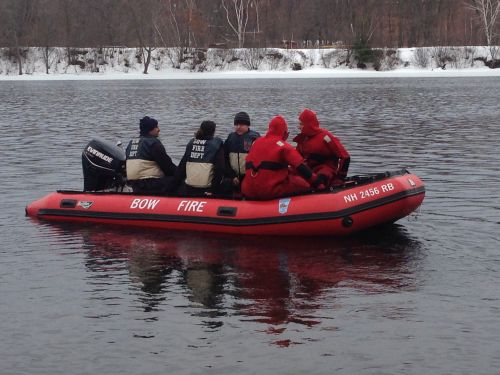 Explorers and instructors practicing ice rescues from a boat on partially iced over water