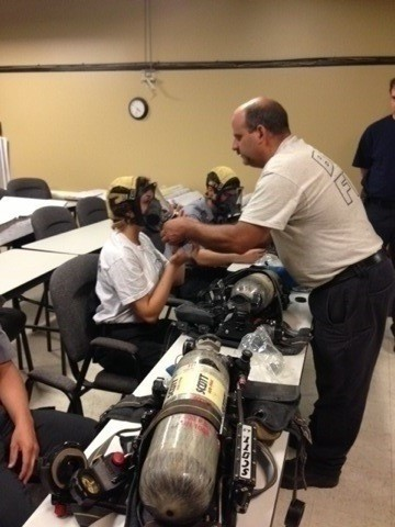 Explorers and instructor learning about fire department breathing equipment
