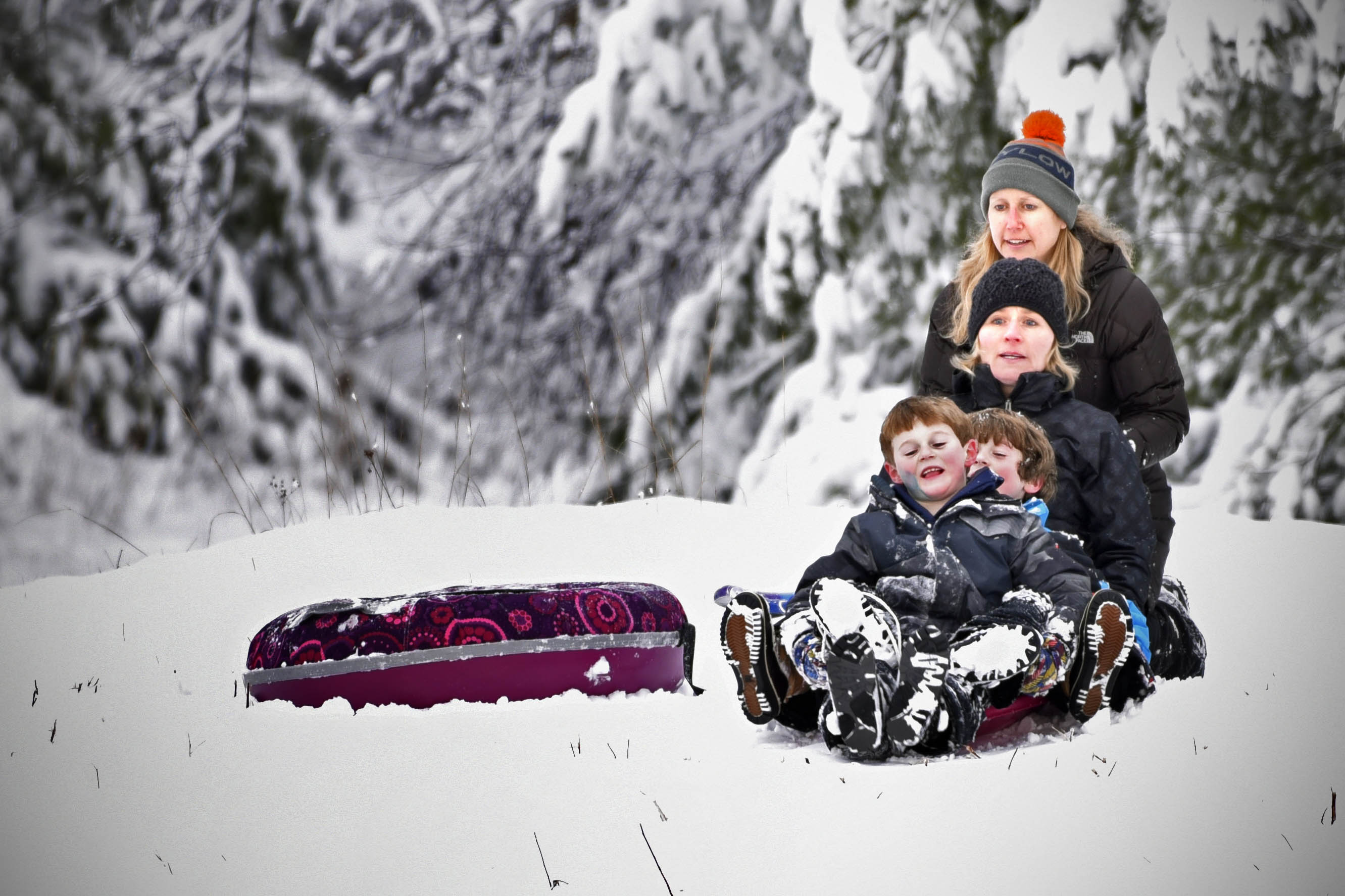Mother pushing children on their snow sled