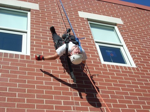 Police Explorer hanging upside down from brick building in climbing gear